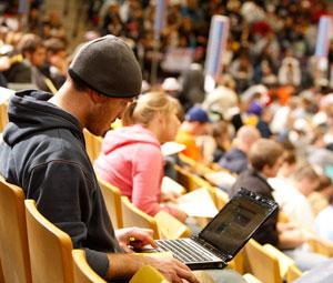 Student in bleachers with laptop at mock election