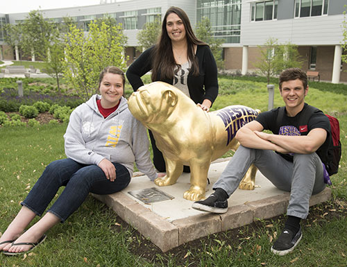 three students with Rocky statue