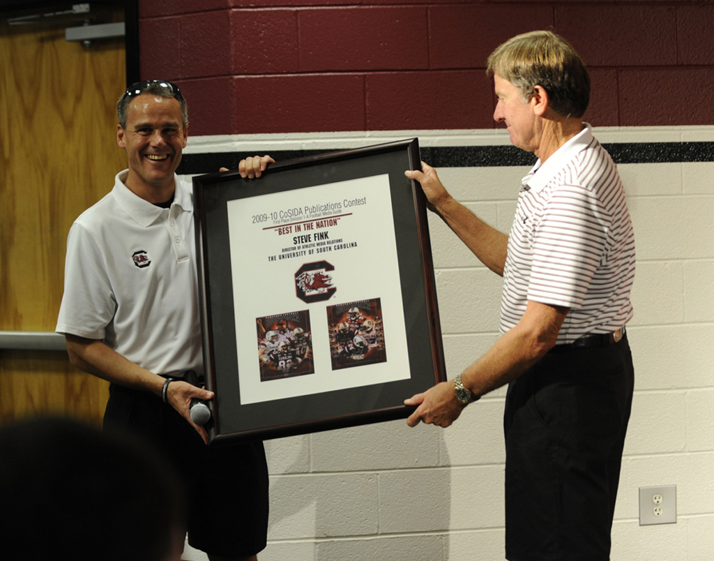 "Steve Fink receiving a plaque from Steve Spurrier for having his 2009 football media guide voted ""Best in the Nation"""