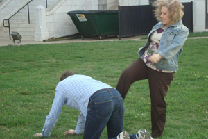 A woman pretends to kick a man on the ground.