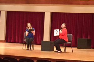 Two women sing while holding portraits of men.