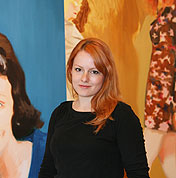 Picture of Kristin in front of her paintings.
