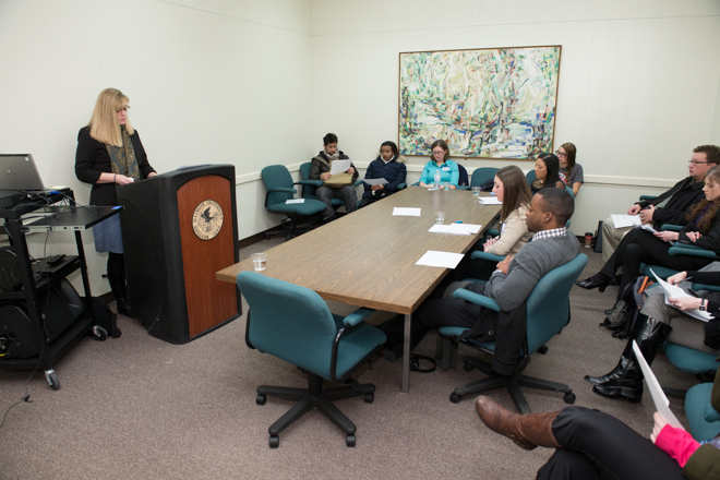 Female student speaking to a group in a conference room