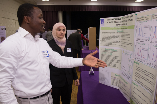 Two students discussing information contained on a presentation board