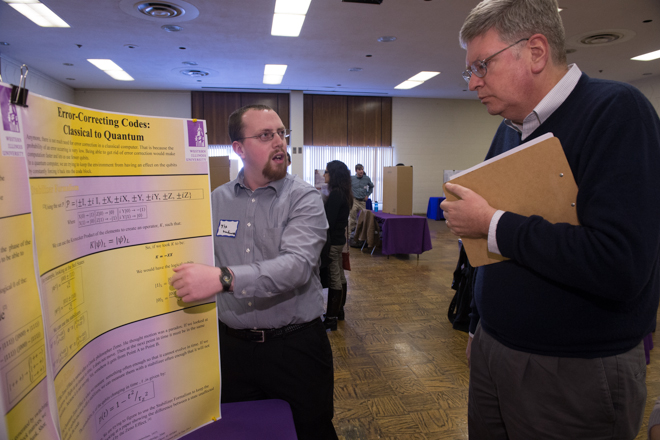 Student presenting his information to a faculty member