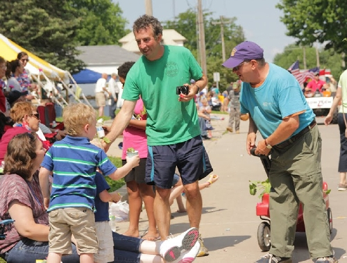 Western Illinois University School of Agriculture's Joel Gruver (green shirt) and members of the Macomb Community Garden distributed plants to Heritage Days parade goers in Macomb last Saturday. Photo courtesy of Abby Wendle.