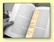 image of a hand holding a book with a yellow bookmark