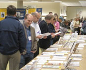 Photograph of people looking at publications from the 2012 WIU Author Recognition Reception.