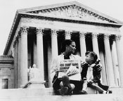 Photo of a woman and a small girl sitting on the steps of a court house holding a newspaper that reads High Court Bans Segregation In Public Schools.