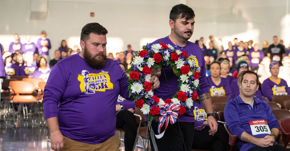 Photo of two people caring a wreath from the 7th Annual Fallen Soldiers 5k event
