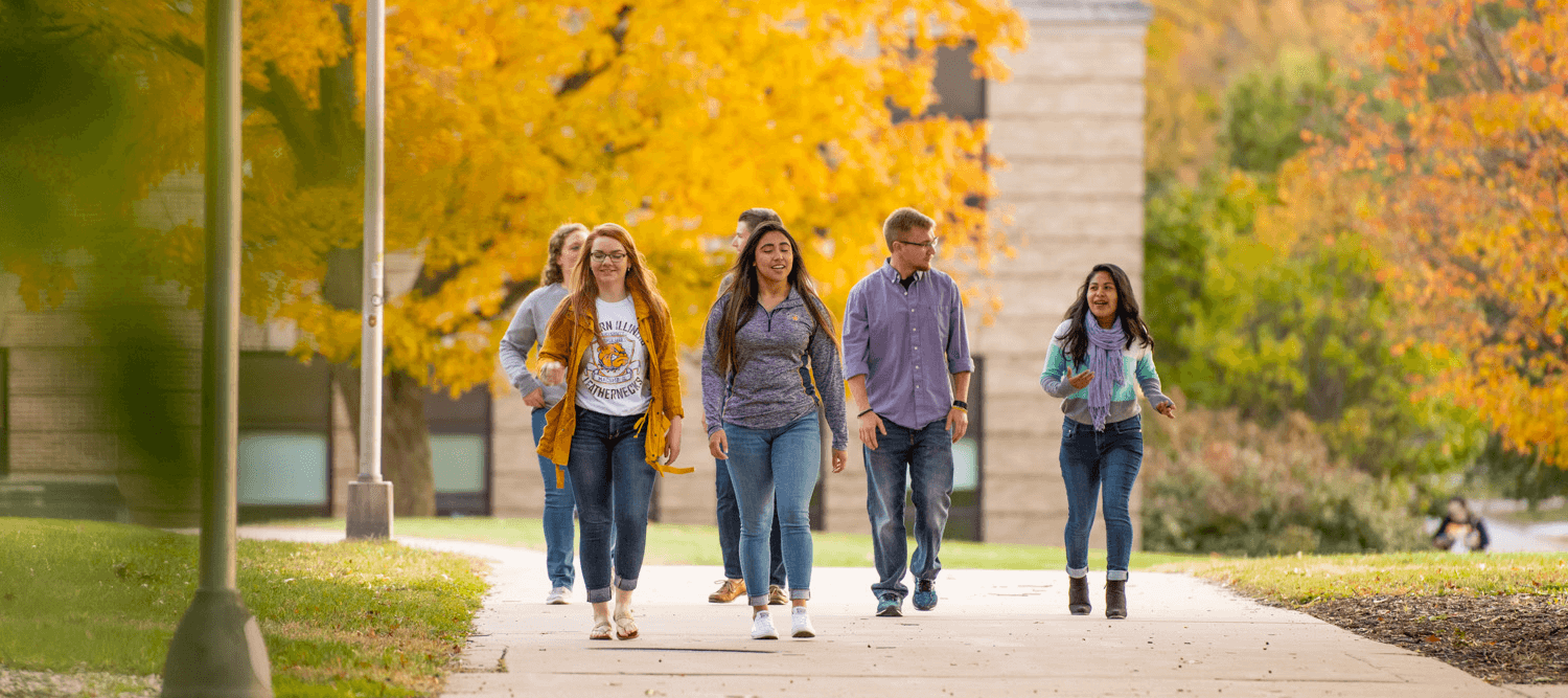 A group of students walking down a sidewalk.