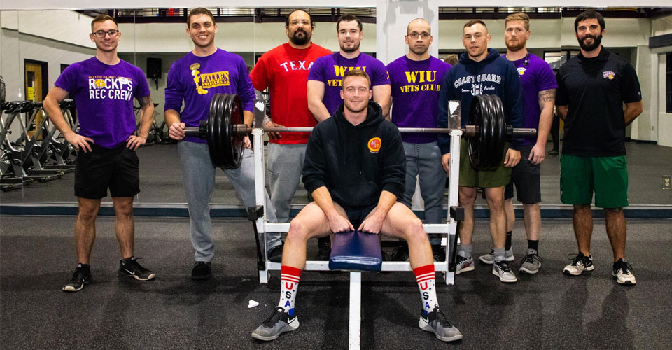 Photo of people posed in a weight room from the Veterans Club vs ROTC Military Appreciation Week Competitions